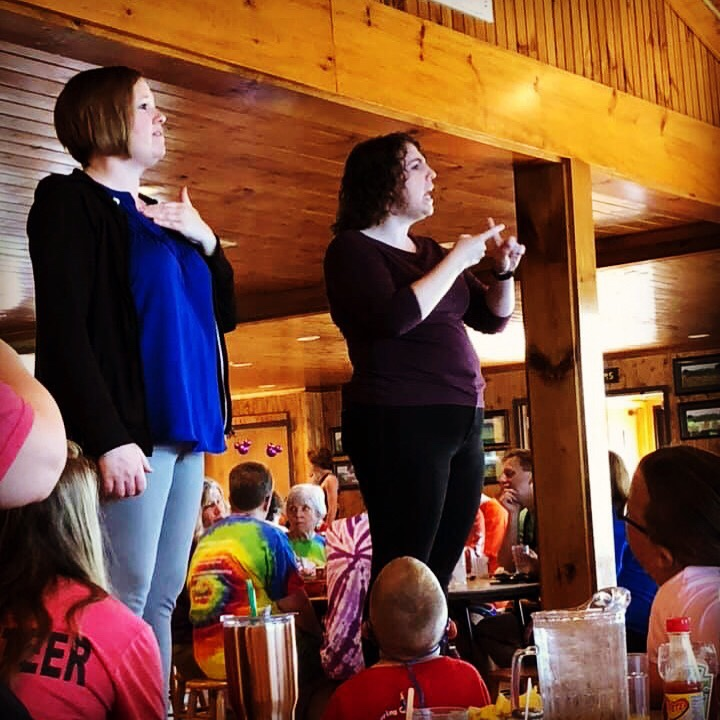 In the Camp Cheerio dining hall, Amy, left, transliterates announcements into Cued American English, while Taylor, right, interprets into American Sign Language. The dining hall structure is honey-colored wood all around There are several families in the background at the bottom of the picture. Amy and Taylor are standing on stools, so they are elevated above the crowd for easier viewing. Amy is a white female with chin-length reddish-blonde hair. She is wearing light denim jeans, a jewel-blue shirt, and a black long-sleeved jacket. Taylor is a white female, with shoulder-length, brown, curly hair. She is wearing black jeans and a three-quarter sleeve dark purple shirt.