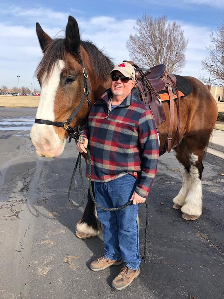 "A man stands next to a Clydesdale horse in a paved lot. There is a blue sky and couple of bare trees in the background, as it is winter. The horse is mostly brown, with a white face stripe between the eyes, from the forelock to the muzzle, and white ""socks"". The man is tall, and wears blue jeans and a red, tan, and blue long-sleeved pullover. He has on hiking shoes, sunglasses, and a"