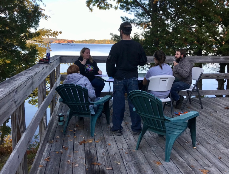 Several people sit around a table that is outside on a deck. The deck overlooks trees and a lake in the background. A blond woman in a dark, long-sleeved shirt sits, facing the camera, with her right hand in the number five shape, at the side position. Across from her, a woman with short red hair, wearing a grey hoodie, sits with her back to the camera. Next to her, a man with dark hair stands, wearing blue jeans, a dark, long-sleeved shirt, and a naseball cap. Next to him, a woman sits. Shes got long, dark hair, swept into a ponytail. She's wearing a grey t-shirt. At the end of the table, in profile view, sits a man with dark hair and a beard. He is wearing a dark pullover top and blue jeans.